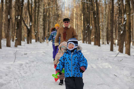 Kid running in a winter park and have fun with family Standard-Bild