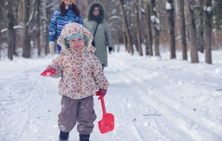 Kid playing games in a winter park and have fun with family Standard-Bild