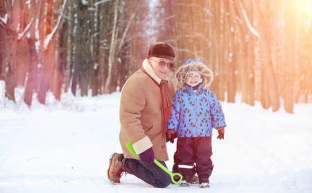 Winter park sotto la neve. Passeggiata mattutina a gennaio attraverso la foresta. Famiglia a piedi nel parco invernale.