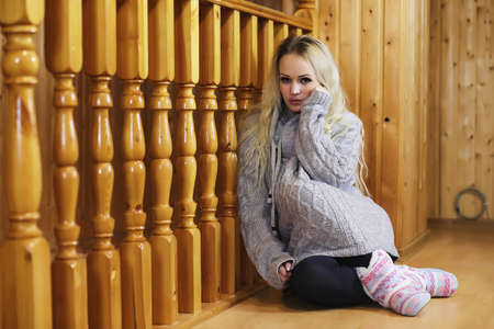 A young girl sits on a ladder in a sweater Stockfoto