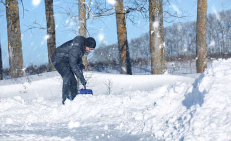 man remove snow with shovel from the road in snowy winter