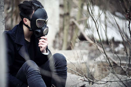 The guy in the coat and gas mask. Post-apocalyptic portrait Asian masked from radiation. The boy is Korean in a mask from poisoning with gases. Post-nuclear mask on the Asian.