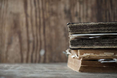Old books on a wooden table and magnifier