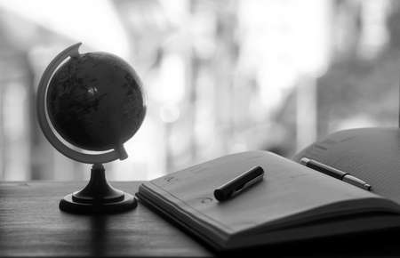 A pen on the desk with small globe