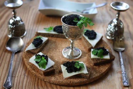 snack black caviar on a wooden brown background