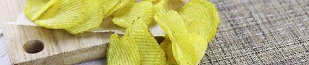 Horizontal bakground of potato chips on a white table Stock Photo