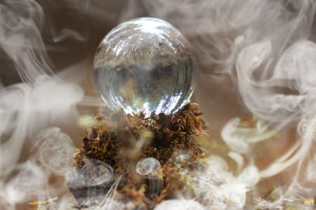 A crystal ball in the smoke. A magical accessory in the woods on the stump. Ritual ball of witches and sorcerers on an old rotten stump.