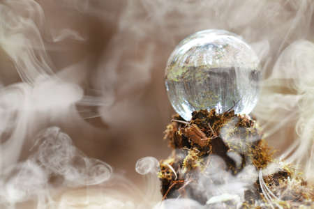 A crystal ball in the smoke. A magical accessory in the woods on the stump. Ritual ball of witches and sorcerers on an old rotten stump.  Stock Photo