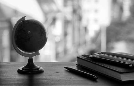 A pen on the desk and a small blue globe