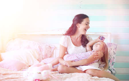 Young girl reads a book Young girl with a daughter are sitting o Stock Photo