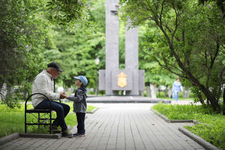 Grandpa is walking with her grandson in a spring park. Grandson