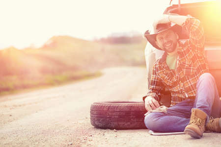 Man is sitting on the road by the car Stock Photo