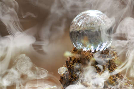 A crystal ball in the smoke. A magical accessory in the woods on Zdjęcie Seryjne - 96449791