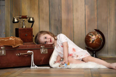 A child in a retro interior and an old phone sits on the floor. Foto de archivo