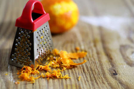 grater zest of citrus fruit and on wooden table