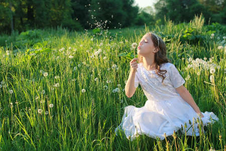 Teen blowing seeds from a dandelion flower in a spring park Stock Photo