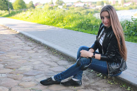 Young girl on a walk. Girl in a leather jacket on the street. Be Stock Photo