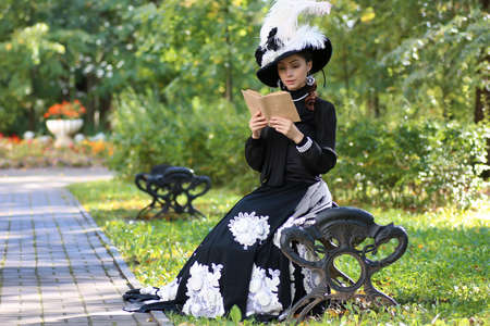 girl in retro dress past century read letter on the bench