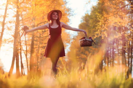 A girl in a hat on a walk in the park. A girl with a basket walk Stock Photo