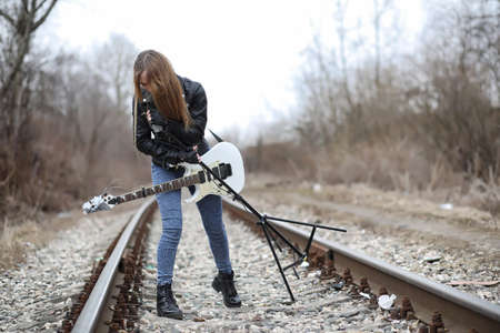 A rock musician girl in a leather jacket with a guitar Standard-Bild - 97769237