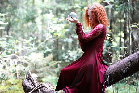 The red-haired witch holds a ritual with a crystal ball Stockfoto