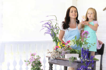 Florist girl who creates a bouquet of flowers standing on a wooden table Stock Photo