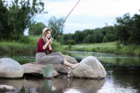 Girl by the river with a fishing rod Archivio Fotografico