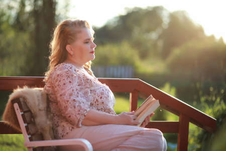 An elderly woman on the porch of a house Stock Photo
