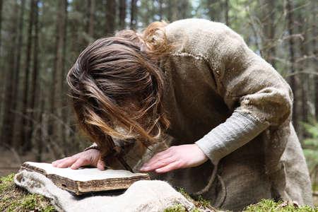 A man in a cassock spends a ritual in a dark forest