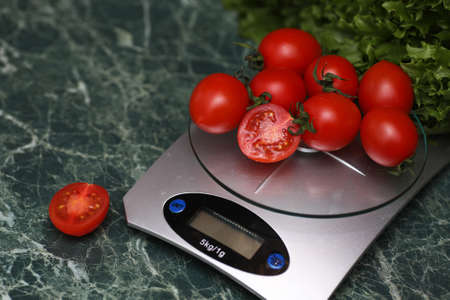 Fresh tomatoes on kitchen scales weighing