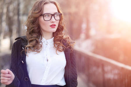 Girl business woman in the spring on a walk in a coat Stock Photo