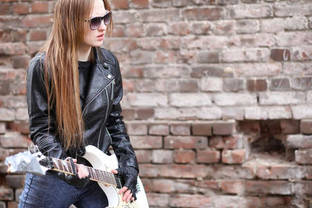 A rock musician girl in a leather jacket with a guitar