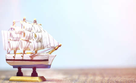 Old wooden ship with sails and masts toy on a stand. Vintage and Stock Photo