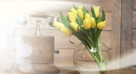 bouquet of yellow tulips in a vase on the floor Stock Photo