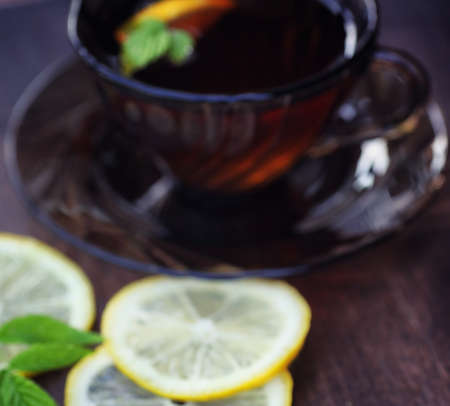 Tea with lemon and mint in nature. A cup of hot mint tea with le Stock Photo