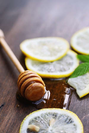 On a wooden texture background a lemon and honey