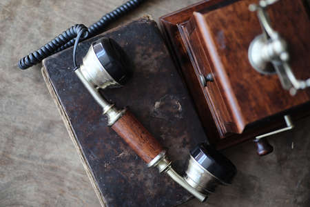 Old telephone and retro book on a wooden table