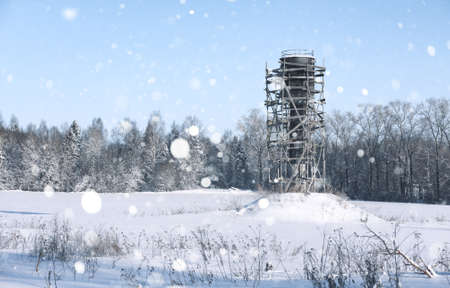 Scaffold around the water tower in field in front of forest in s Stock fotó