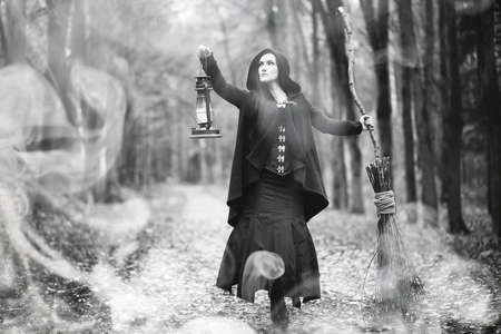 Woman in a witch suit in a dense forest Stock fotó