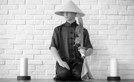 Asian novice on a white brick wall