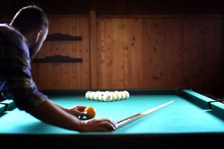 A man with a beard plays a big billiard. Party in a 12-foot pool Фото со стока