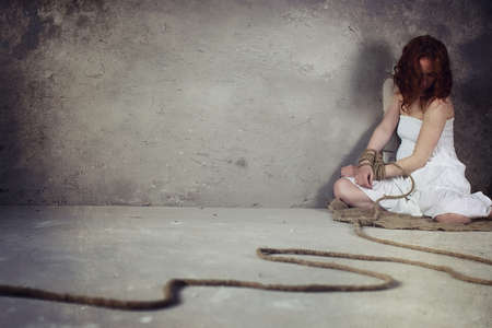 An abducted young girl tied up on the floor
