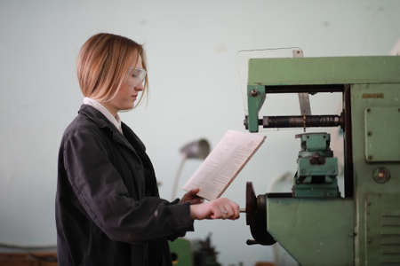 Young woman engineer working at machine tool Archivio Fotografico