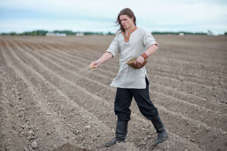 A young peasant sows the field with grain