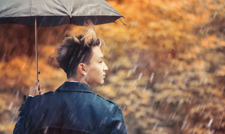 Autumn rainy weather and a young man with an umbrella