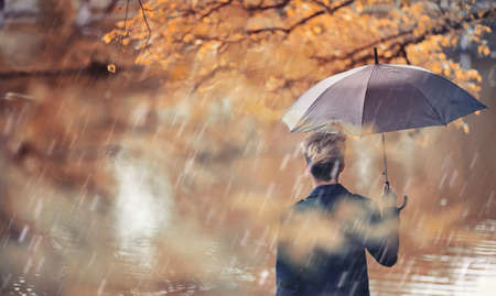 Autumn rainy weather and a young man with an umbrella Standard-Bild - 108415353