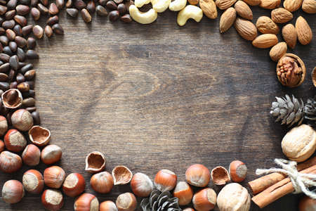 Different nuts on a wooden table. Cedar, cashew, hazelnut, walnuts and a spoon on the table. Many nuts are inshell and chistchenyh on a wooden background