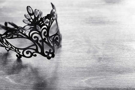 Carnival mask on the table. The subject of camouflage on date during a carnival. Venetian mask on a wooden table in black and white. 版權商用圖片