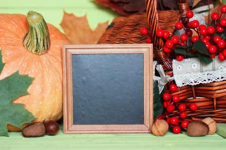 Thanksgiving concept. A pumpkin, cherries replica and a small square chalkboard 版權商用圖片