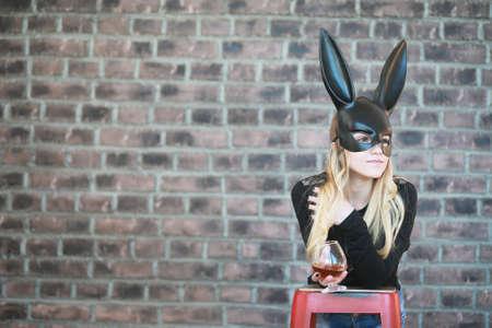 Una chica con una máscara negra con orejas largas en el estudio.